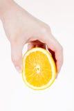 Mano femenina aislada que exprime el limón Fotografía de archivo libre de regalías