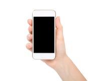 Mano femenina aislada que sostiene el teléfono blanco del tacto Foto de archivo
