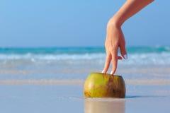 Mano femenina apoyada en el coco en fondo del mar Imagen de archivo