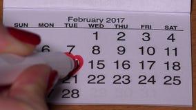 Mano femenina con drenaje rojo del marcador una forma del corazón en calendario el 14 de febrero almacen de metraje de vídeo
