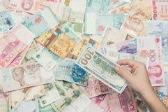 Mano femenina con el dinero de Asia sudoriental y del billete de dólar del americano ciento La moneda de Hong Kong, Indonesia, Ma Fotografía de archivo libre de regalías