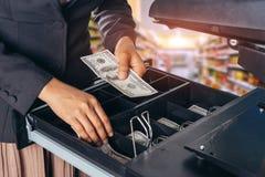 Mano femenina con el dinero en tienda del supermercado Dólar americano Dólar de EE. UU. Imágenes de archivo libres de regalías