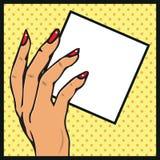 Mano femenina con el espacio en blanco del papel o de la tarjeta en su illustr del arte pop de la mano Imagen de archivo libre de regalías