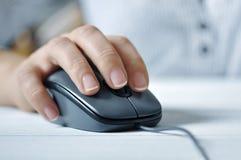 Mano femenina con el ratón del ordenador Fotos de archivo libres de regalías