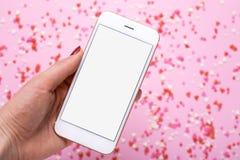 Mano femenina con el teléfono móvil en fondo con rosa y los corazones rojos imagen de archivo