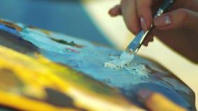 Mano femenina con la brocha Pinturas de aceite de mezcla de la mujer en la paleta del artista almacen de video