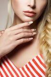Mano femenina con la manicura Pelo rubio hermoso Fotografía de archivo