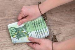 Mano femenina con las esposas que sostienen 100 billetes de banco euro Foto de archivo libre de regalías