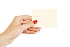 Mano femenina con los clavos rojos que sostienen una tarjeta en blanco Imágenes de archivo libres de regalías