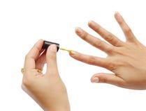 Mano femenina con un esmalte de uñas de oro en el fondo blanco Fotos de archivo libres de regalías