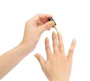 Mano femenina con un esmalte de uñas de oro en el fondo blanco Imágenes de archivo libres de regalías