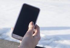 Mano femenina con un smartphone en el fondo de la nieve el concepto de una conversación o de una fotografía video imagen de archivo libre de regalías