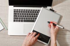 Mano femenina con una aguja en una tableta gráfica, ordenador portátil abierto en una tabla ligera, visión superior Fotos de archivo libres de regalías