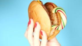 Mano femenina con una manicura, sosteniendo una hamburguesa con la piruleta, en un fondo azul primer metrajes