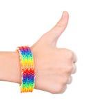 Mano femenina con una pulsera modelada como la bandera del arco iris que muestra los pulgares para arriba En blanco Fotos de archivo libres de regalías