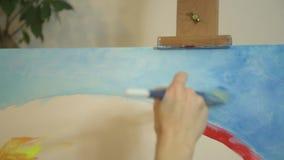 Mano femenina del artista que mezcla colores de acrílico con el cepillo en una paleta almacen de metraje de vídeo