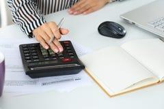 Mano femenina del contable que sostiene la pluma de plata Fotos de archivo libres de regalías