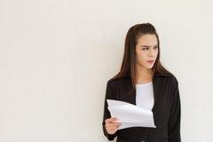 Mano femenina del ejecutivo de operaciones que lleva a cabo el documento con el FE negativo Imagen de archivo