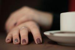 Mano femenina del primer en la taza de la tabla y de café Fotografía de archivo libre de regalías