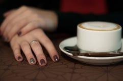Mano femenina del primer en la taza de la tabla y de café Fotografía de archivo