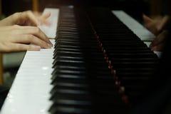 mano femenina del primer que juega el piano de cola imagen de archivo