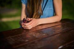 Mano femenina del ` s que sostiene los vidrios en la tabla de madera Imagen de archivo libre de regalías