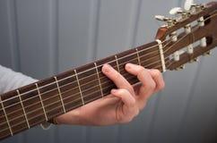 Mano femenina en la guitarra del fretboard foto de archivo
