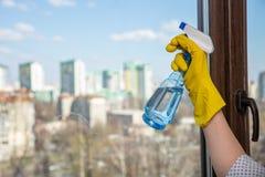 Mano femenina en los guantes amarillos que limpian la ventana con el detergente del espray E imagenes de archivo