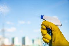 Mano femenina en los guantes amarillos que limpian la ventana con el detergente del espray E foto de archivo