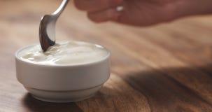 Mano femenina joven que come el yogur del melocotón con la cuchara Imagen de archivo libre de regalías