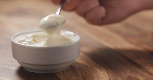 Mano femenina joven que come el yogur del melocotón con la cuchara Fotografía de archivo