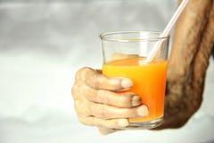 Mano femenina mayor que sostiene un vidrio de zumo de naranja Fotografía de archivo