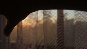 Mano femenina que abre la cortina transparente en el cierre de la puesta del sol de la salida del sol metrajes
