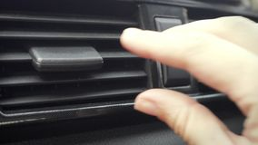 Mano femenina que ajusta la dirección de la aleta del aire acondicionado en coche almacen de video