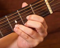 Mano femenina que aprende el acorde de la guitarra Imagen de archivo