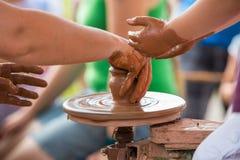 Mano femenina que ayuda a hacer el jarro de cerámica en un children& x27 de la rueda; manos de s Imágenes de archivo libres de regalías