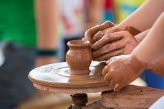 Mano femenina que ayuda a hacer el jarro de cerámica en un children& x27 de la rueda; manos de s Imagenes de archivo