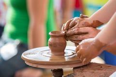 Mano femenina que ayuda a hacer el jarro de cerámica en un children& x27 de la rueda; manos de s Fotos de archivo libres de regalías