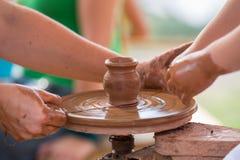Mano femenina que ayuda a hacer el jarro de cerámica en un children& x27 de la rueda; manos de s Imagen de archivo libre de regalías