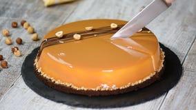 Mano femenina que corta la torta de la crema batida del caramelo Torta del caramelo, postre de la crema batida en una placa almacen de video