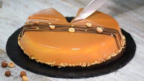 Mano femenina que corta la torta de la crema batida del caramelo Torta del caramelo, postre de la crema batida en una placa almacen de metraje de vídeo