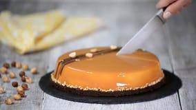Mano femenina que corta la torta de la crema batida del caramelo Torta del caramelo, postre de la crema batida en una placa metrajes