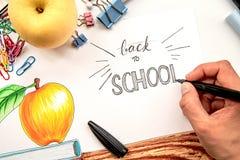 Mano femenina que dibuja letras de nuevo a escuela en el ejemplo con el fondo blanco con los libros y la manzana Imagen de archivo