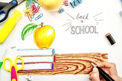 Mano femenina que dibuja un ejemplo con el fondo blanco con los libros, manzana de los marcadores y poniéndolo letras de nuevo a  Foto de archivo libre de regalías