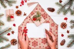 Mano femenina que escribe una letra a Papá Noel en fondo del día de fiesta con Fotos de archivo