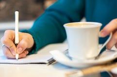 Mano femenina que firma en cuaderno y café de consumición, en fondo brillante Imagen de archivo