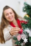 Mano femenina que hace el adornamiento del árbol de navidad Imagenes de archivo