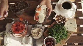 Mano femenina que hace el bocadillo con hummus y los salmones para la opinión superior del desayuno Día asoleado metrajes
