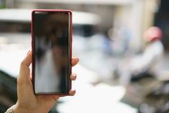 Mano femenina que lleva a cabo el negro del smartphone imágenes de archivo libres de regalías