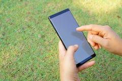 Mano femenina que lleva a cabo el negro del smartphone imagenes de archivo